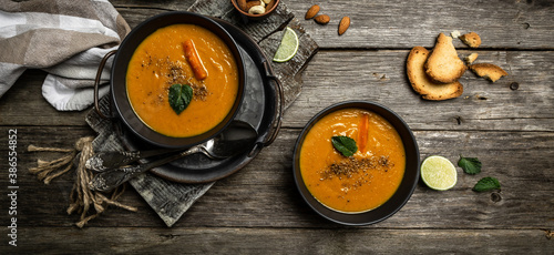 A bowl of homemade fresh spicy organic creamy pumpkin soup with baked carrots, peppers and cheese, lime juice and ginger Billede på lærred