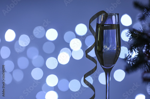 Glass of champagne with Christmas decor against blurred lights