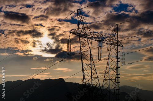Obraz na plátně Current pylon in silhouette at sunset in the hills