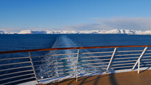 Panorama View From The Stern Of A Cruise Ship With The Vessel's Wake In The Arctic Ocean And Snow-covered Mountains On The Horizon Near Hammerfest, Norway, Scandinavia In Winter Time.