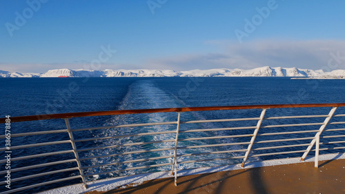 Photo Panorama view from the stern of a cruise ship with the vessel's wake in the arctic ocean and snow-covered mountains on the horizon near Hammerfest, Norway, Scandinavia in winter time