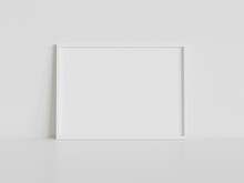 White Frame Leaning On White Floor In Interior Mockup. Template Of A Picture Framed On A Wall 3D Rendering