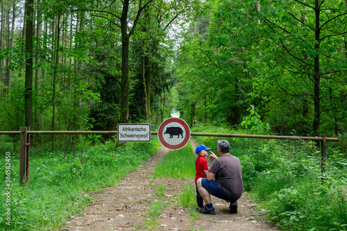 Father and son are standing in the forest on a path that is closed with a barrier Poster Mural XXL