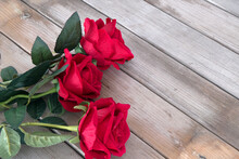 Three Red Roses On Wood Grain ...