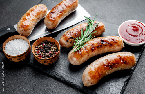 grilled sausages with spices on a stone background Fotobehang
