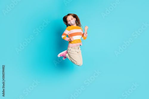 Obraz Full length photo of pretty cheerful girl jumping wear mask casual outfit isolated over bright blue color background - fototapety do salonu
