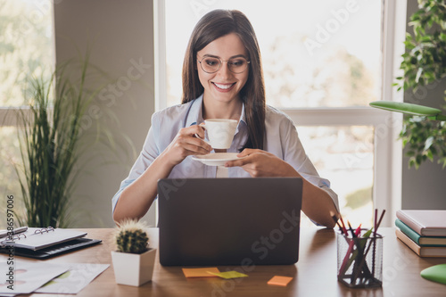 Obraz Photo of charming lady sit desktop arms hold cup saucer beaming smile look screen pc wear specs shirt in home office indoors - fototapety do salonu