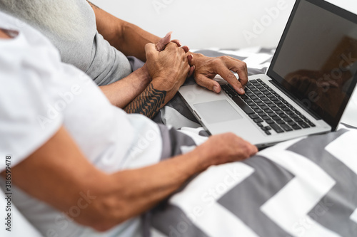 Senior couple using portable computer in bed - Mature people having fun with lap Fototapete