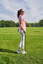 Female Golfer With A Club Staring Into The Distance