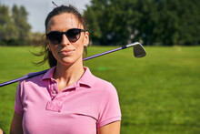 Woman With A Golf Club Standing Outside