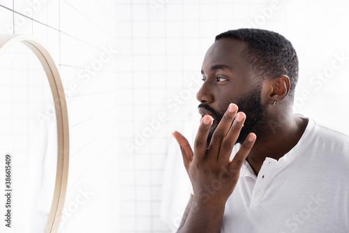 Fényképezés afro-american man applying cure for strengthening beard growth