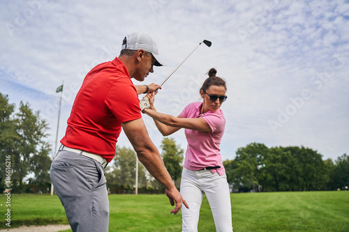 Obraz Golfer mastering a swing technique assisted by her coach - fototapety do salonu