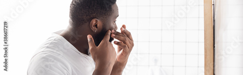 panoramic shot of afro-american man trying squeeze pimple Fotobehang