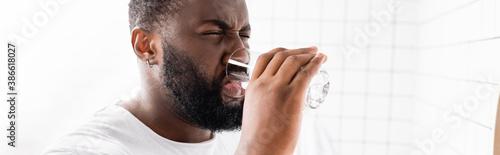 Obraz panoramic shot of afro-american man grimacing and drinking water - fototapety do salonu
