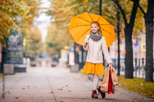 Foto girl with a bright jelly umbrella and with shopping guide walks along the autumn city boulevard smiling happily