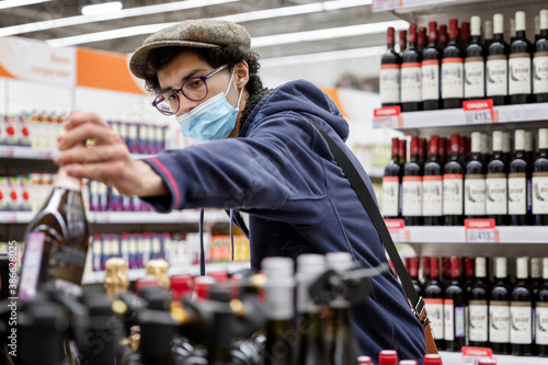 Photo A young man in a medical mask chooses wine in a supermarket