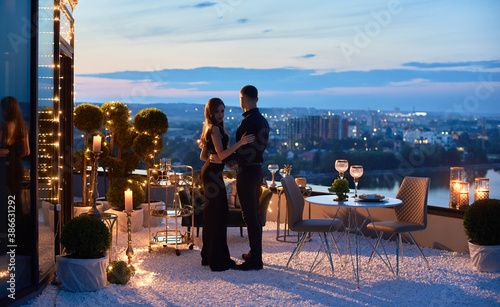 Attractive young woman and man having romantic date at rooftop restaurant Fotobehang
