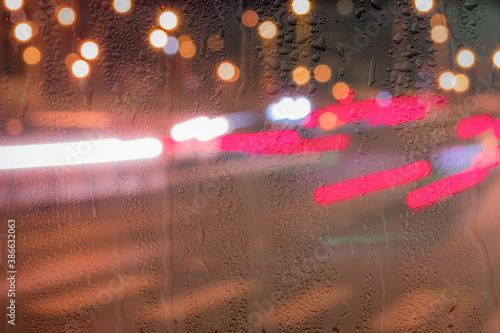 Defocused headlights from moving cars behind rainy, wet glass at night Wallpaper Mural