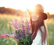 Girl with lupines in shirt and hat at sunset