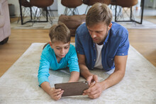 Man And Son Using Digital Tablet At Home