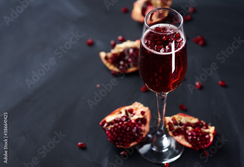 Christmas Mimosa cocktail with champagne and pomegranate on a dark table