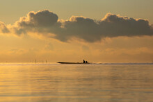 Fishermen On Wooden Boat During Sunrise In Thailand.