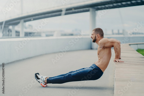 Sideways shot of muscular man does reverse push up exercise, trains arms, keeps Wallpaper Mural