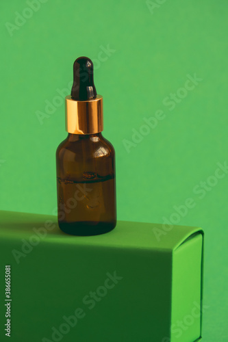 Obraz glass bottle with cosmetic product with pipette on a green pedestal on a green background - fototapety do salonu