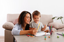Young Beautiful Woman Teaching Her Two Year Old Son To Draw At Home. Woman Spending Quality Time With Her Toddler Child. Close Up, Copy Space, Background.