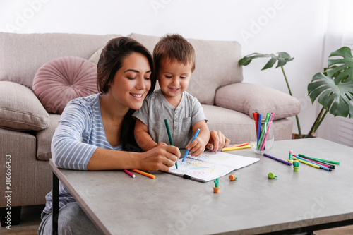 Photographie Young beautiful woman teaching her two year old son to draw at home