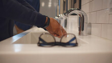 Close Up Of Man Putting Glasses On Top And Washing Hands In Public Toilet