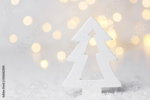 Fotografie, Obraz Wooden ornament Christmas tree in forest golden bokeh garland lights snow