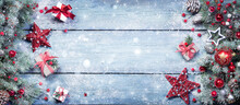 Fir Branches With Red Ornament And Rustic Giftbox On Snowy Plank - Christmas Background