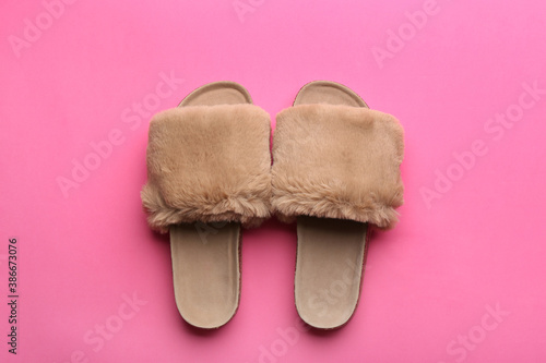 Pair of soft slippers on pink background, flat lay