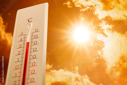 Fotografiet Weather thermometer showing high temperature and sunny sky with clouds on backgr