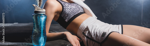 Obraz Website header of sportswoman with towel near tire and sports bottle in gym with some - fototapety do salonu