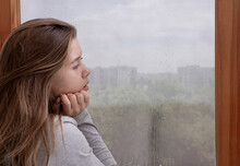 Sad Young Woman Looking Out Wi...