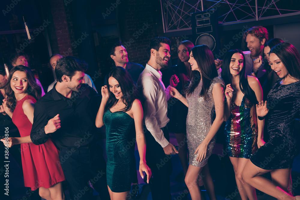 Fototapeta Portrait of nice elegant cheerful beautiful handsome colleagues having fun dancing celebrating corporate festive visiting dark night club indoors