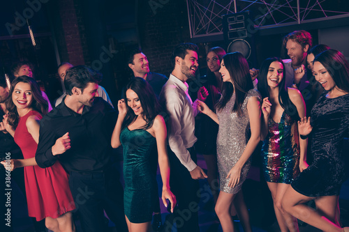 Portrait of nice elegant cheerful beautiful handsome colleagues having fun dancing celebrating corporate festive visiting dark night club indoors - 386688806