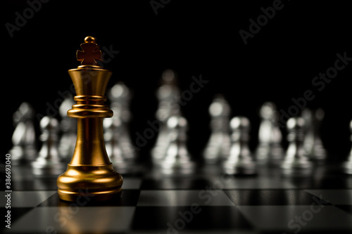 Obraz Golden King chess standing in front of other chess, Concept of a leader must have courage and challenge in the competition, leadership and business vision for a win in business games - fototapety do salonu