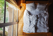 Bed With White Bedding In Wood...