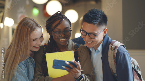 Multiethnic friends in college enjoying watching text or video on mobile phone Fototapet
