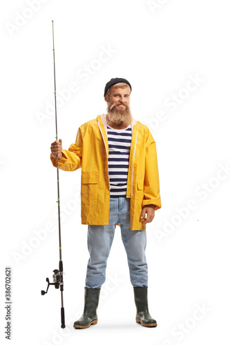 Obraz Full length portrait of a bearded young fisherman holding a fishing rod and smiling - fototapety do salonu