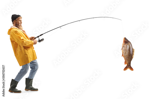 Obraz Full length profile shot of a bearded fisherman catching a big fish - fototapety do salonu