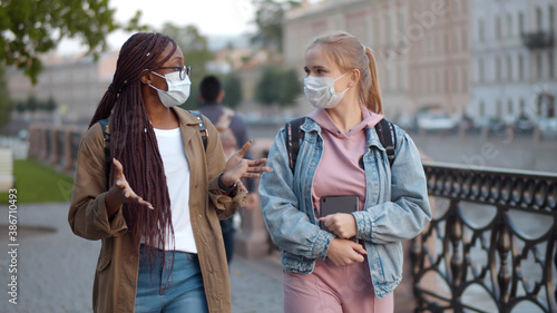 Slika na platnu Multinational student women in medical mask talking walking down city street