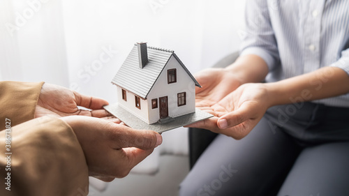 Fotografie, Obraz House model with agent and customer discussing for contract to buy, get insurance or loan real estate or property