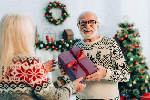 Obraz selective focus of happy senior man looking at camera while presenting christmas gift to wife - fototapety do salonu