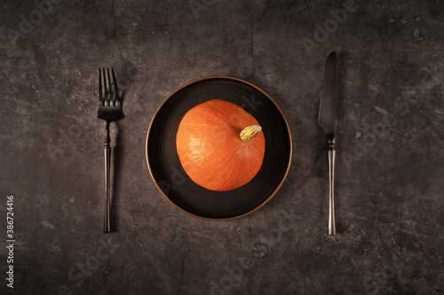 Photographie Vintage template with old metal plate with pumpkin on black stone background for Halloween design