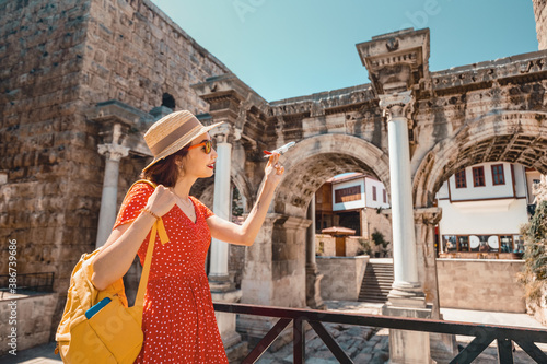 Obraz traveler with a toy plane on the background of the archaeological monument - the gate of the Emperor Hadrian in the old city of Antalya. Concept of air tickets and airlines in Turkey - fototapety do salonu