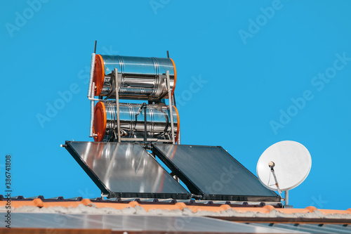 Fotografie, Obraz Solar panels on the roof of the cottage with water barrels and TV or Internet co